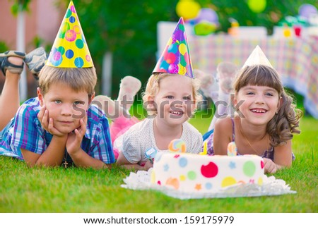 Three little kids celebrating birthday on green grass