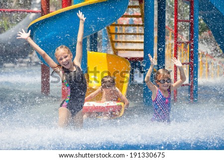 three little kids playing in the swimming pool - stock photo