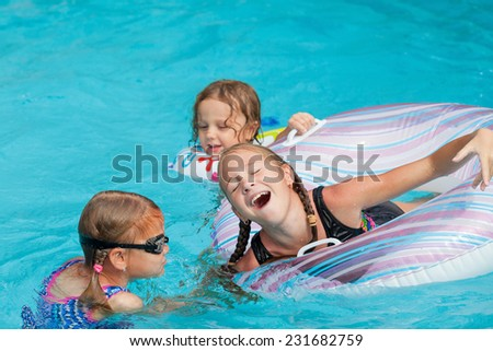 three little kids playing in the swimming pool at the day time