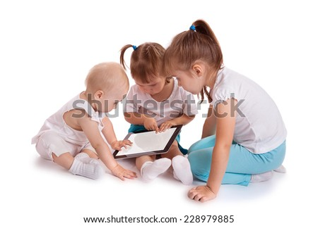 Three little kids playing with tablet PC computer, isolated on white background. Baby hand pointing on touch screen. - stock photo
