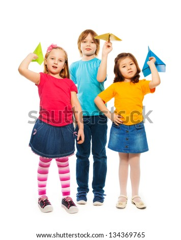Three little kids standing with colorful paper plane, boy and girl, Caucasian and Asian, isolated on white - stock photo