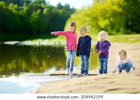 Three little sisters and their brother having fun, laughing and joking by a river at sunny autumn day - stock photo