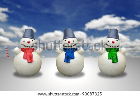 Three little snowman with colorful scarves celebrating Christmas on a cold winter day in the North Pole against a blue cloudy sky. - stock photo