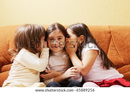 Three little tattlers whispering while sitting on sofa indoors