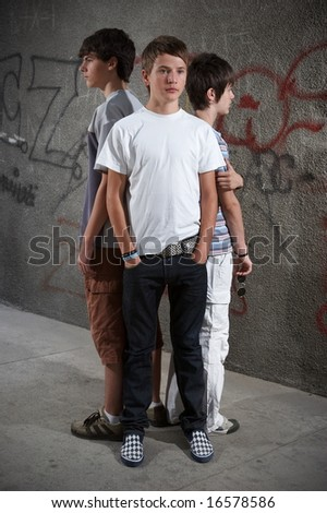 Three loneliness boys standing close in front of graffiti wall - stock photo