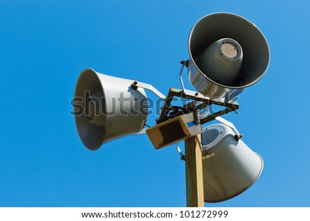 Three loudspeakers on a column against the blue sky - stock photo