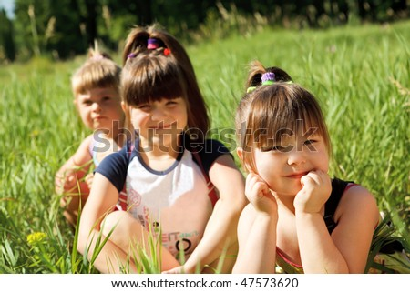 Three lovely girls in the green grass