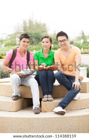 Three lovely high school students studying outdoors - stock photo