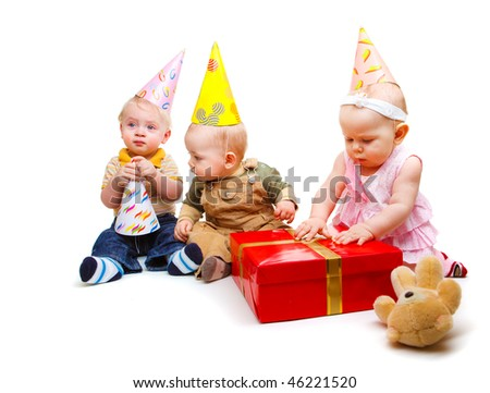 Three lovely toddlers in party hats - stock photo