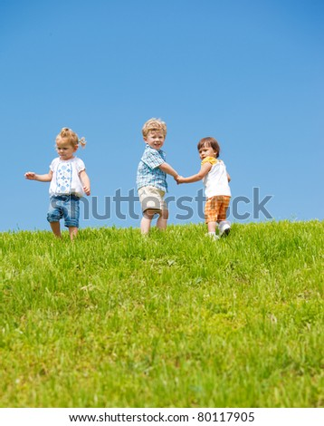 Three lovely toddlers on the hill - stock photo