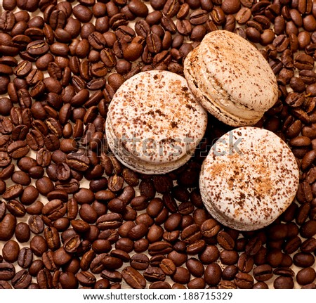 three macaroons on coffee beans background - stock photo