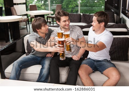 Three male friends drinking cold beer in hot weather. Sitting at the pub   - stock photo