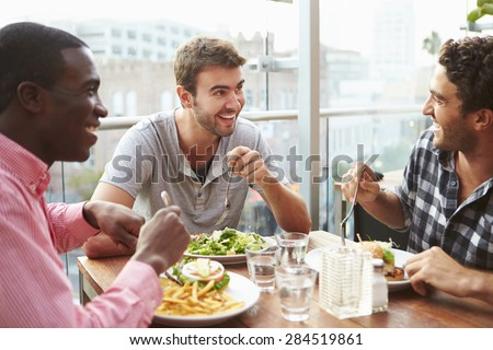 Three Male Friends Enjoying Lunch At Rooftop Restaurant - stock photo