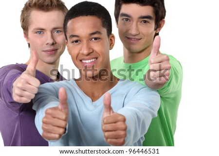 Three male friends giving thumbs-up - stock photo