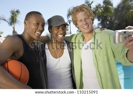 Three male friends making a self-portrait with a photo camera - stock photo
