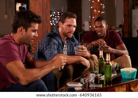 Three male friends playing cards and drinking beer at home