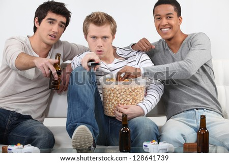 Three male friends watching television together - stock photo