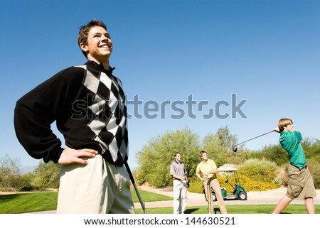 Three male golfers watching other golfer teeing off - stock photo