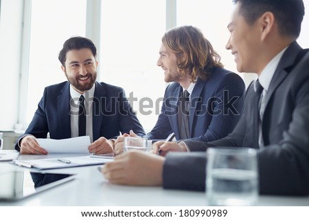 Three managers discussing business plans at meeting
