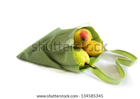 Three mangoes in green, reusable shopping bag on white background - stock photo