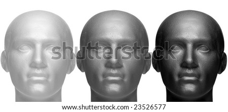 Three mannequin heads in white black and grey, isolated against a white background. - stock photo