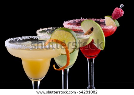 Three Margaritas - apple, orange and raspberry - in chilled glasses over black background, garnished with slice of green apple, limes, orange twist, raspberry and cinnamon stick. - stock photo