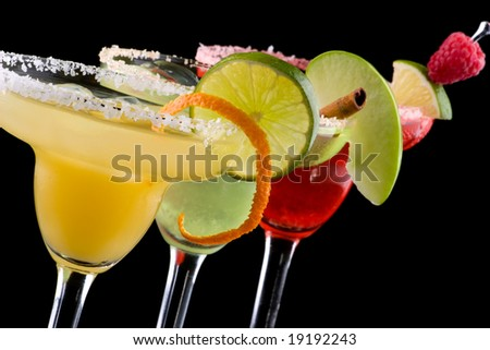 Three Margaritas - apple, orange and raspberry - in chilled glasses over black background. Most popular cocktails series. - stock photo