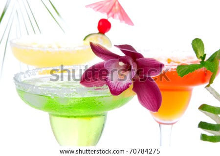 Three Margaritas cocktails composition decorated with lime, orchid, cherry, apple, peach and drink umbrella in margarita glasses  isolated on a white background - stock photo