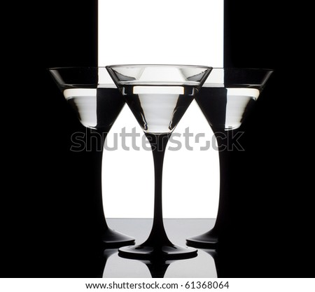 Three martini glass with alcohol on a black, white and black background - stock photo