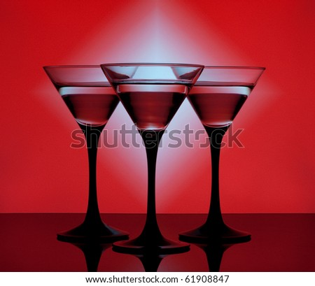 Three martini glass with cocktails on a red background - stock photo