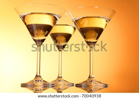 Three martini glasses on yellow background - stock photo