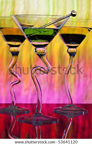 Three martinis in glasses with curved stems in front of colorful lighted background showing shades of yellow, pink, green, red and orange. - stock photo