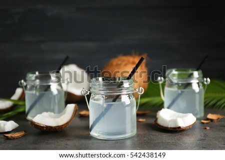 Three mason jars with coconut water and fresh nuts on dark background
