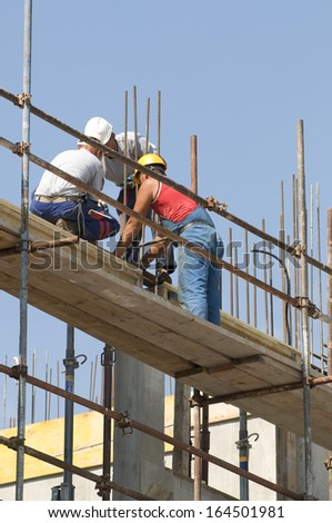 Three masons working on framework of a building under construction - stock photo