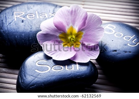 three massage stones - relax, body, soul - and a flower like a concept for wellness, reiki, body care and yoga symbols - stock photo