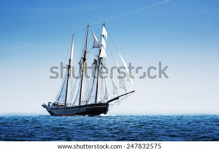 Three mast schooner under sails on the baltic sea. High contrast image. - stock photo