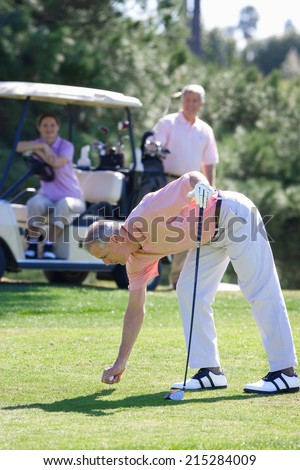 Three mature adults playing golf, mature man in pink polo shirt preparing to tee off, mature couple watching from golf buggy in background - stock photo