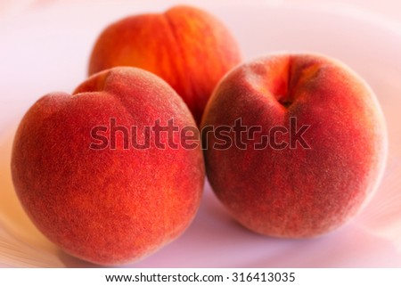 Three mature peaches on a white background.