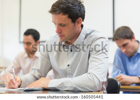 Three mature students taking notes in lecture in college - stock photo