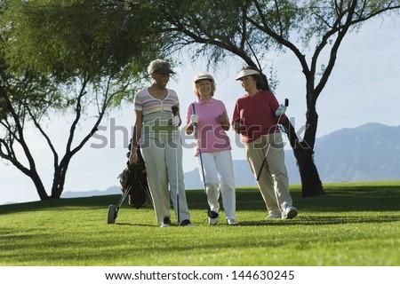 Three mature women walking on golf course - stock photo