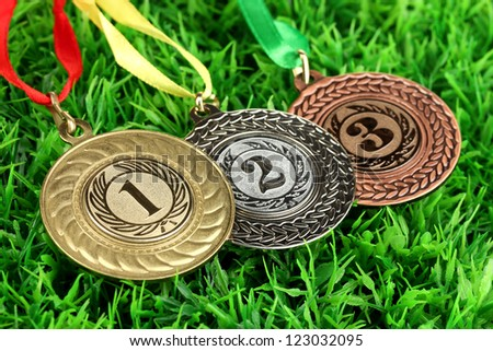 Three medals on grass background - stock photo