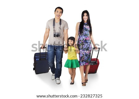 Three member of asian tourist walking in studio while carrying luggage - stock photo