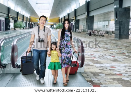 Three member of asian tourist walking on escalator in the airport hall - stock photo
