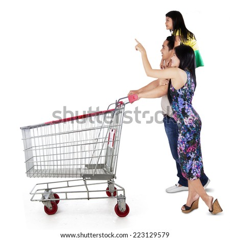 Three member of happy family pushing shopping cart and looking at copyspace - stock photo