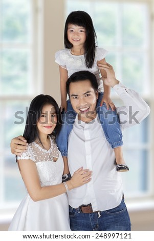 Three member of happy family smiling at camera, shot at home - stock photo