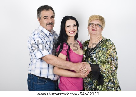 Three members of family father,daughter and mother embracing and smiling in front of image - stock photo
