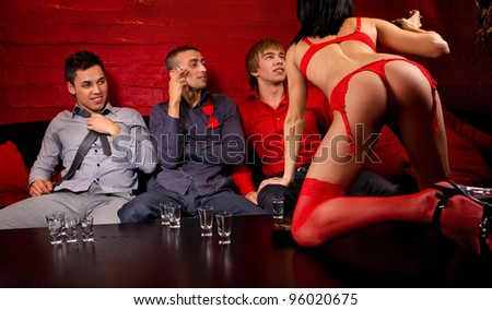 Three men drinking and looking at dancing woman. - stock photo