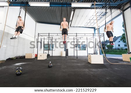 Three men exercise dips with rings - stock photo