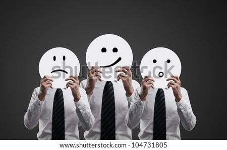three men hold plates with smilies on black  background - stock photo