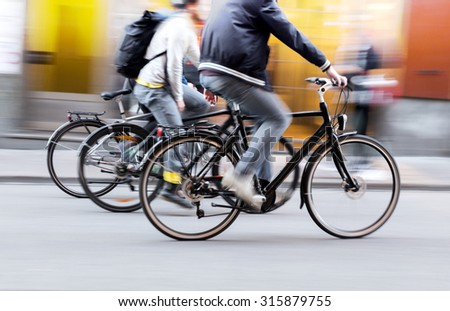 Three men in casual clothes on bicycles in city - stock photo